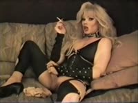 Older seductive shemale Lisa Dupree relaxes and smokes a cigarette while masturbating